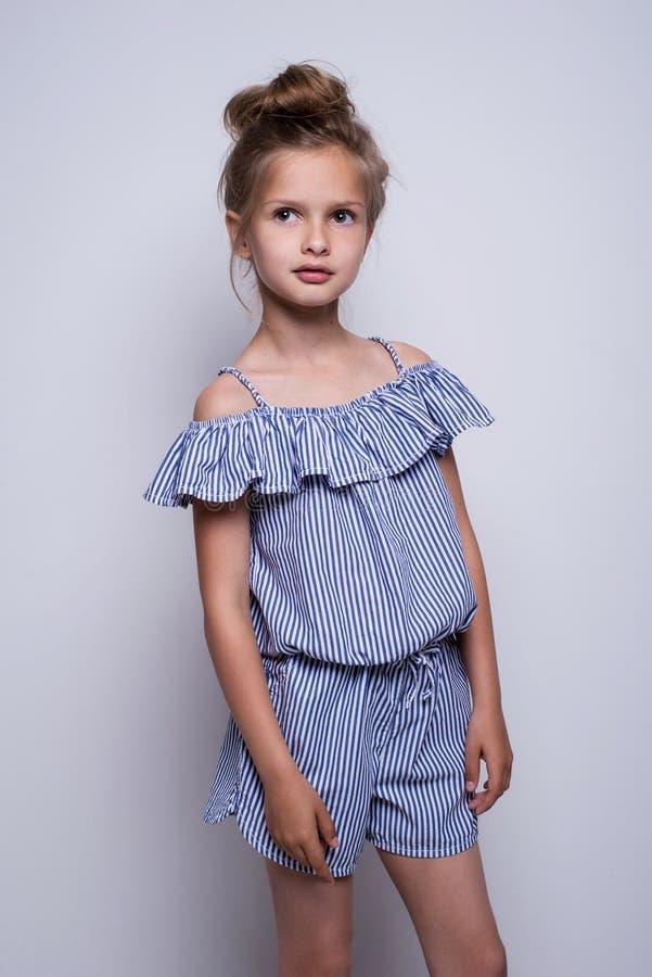 Schönes kleines Art und Weisebaumuster auf weißem Hintergrund Porträt des netten lächelnden Mädchens, das im Studio aufwirft stockfotos