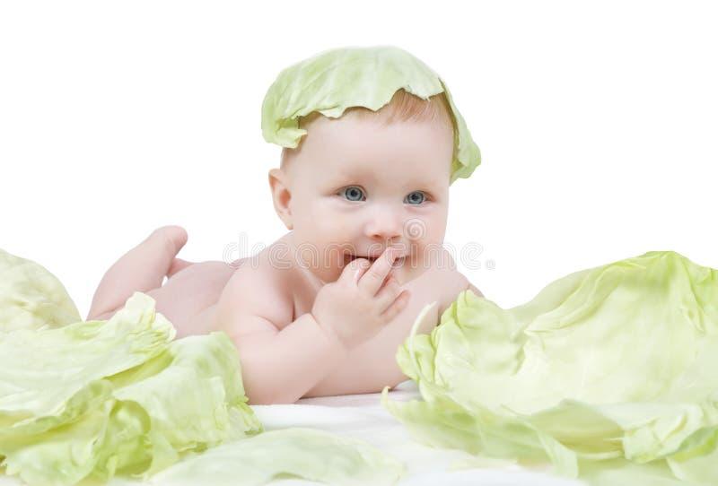 Schönes kleines Baby auf einem weißen Hintergrund mit Grünkohl stockbild