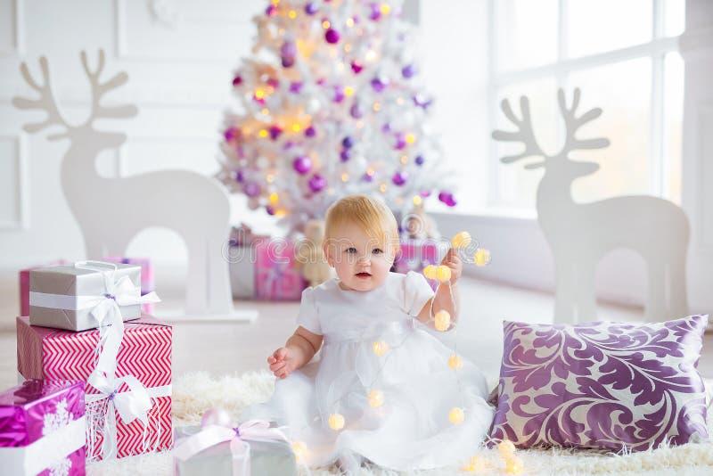 Schönes kleines Baby feiert Weihnachten Neues Jahr ` s Feiertage Süßes Baby im netten Kleid, das Spaß in festlichem hat lizenzfreies stockbild