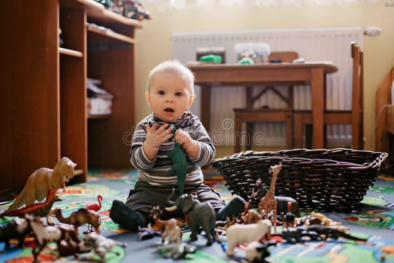Schönes kleines Baby, Kleinkind, das an der Kamera lächeln, Tiere und Dinosaurier um ihn, Innenschuß stockfoto