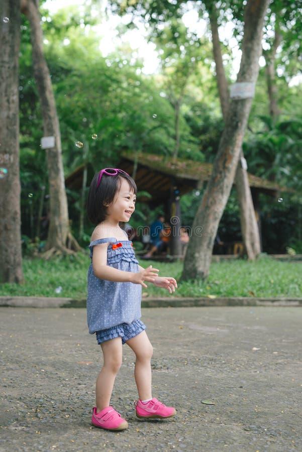 Schönes kleines behaartes Haarmädchen, hat lächelndes Gesicht des glücklichen Spaßes, p stockfoto