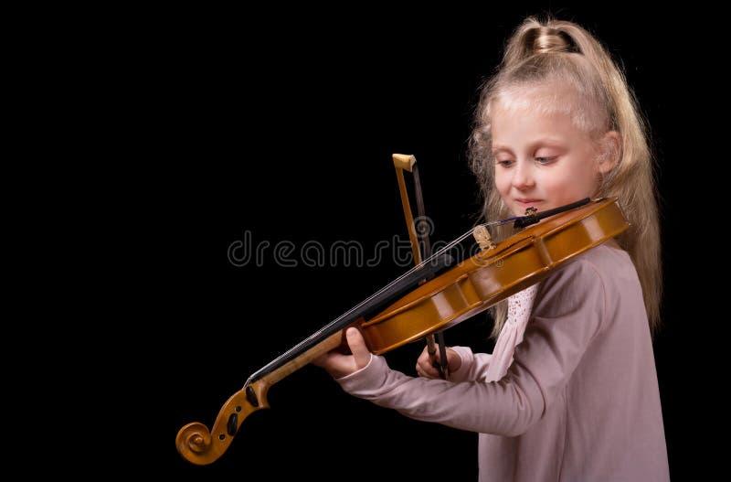 Schönes kleines blondes Mädchen, welches die Violine lokalisiert auf schwarzem Hintergrund spielt lizenzfreies stockfoto