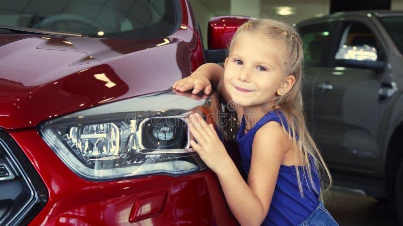 Schönes kleines ist das Mädchen, das auf Autohintergrund aufwirft stockfotografie