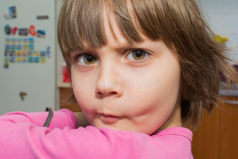 Schönes kleines junges Mädchen, das ein Gesicht macht lizenzfreies stockbild