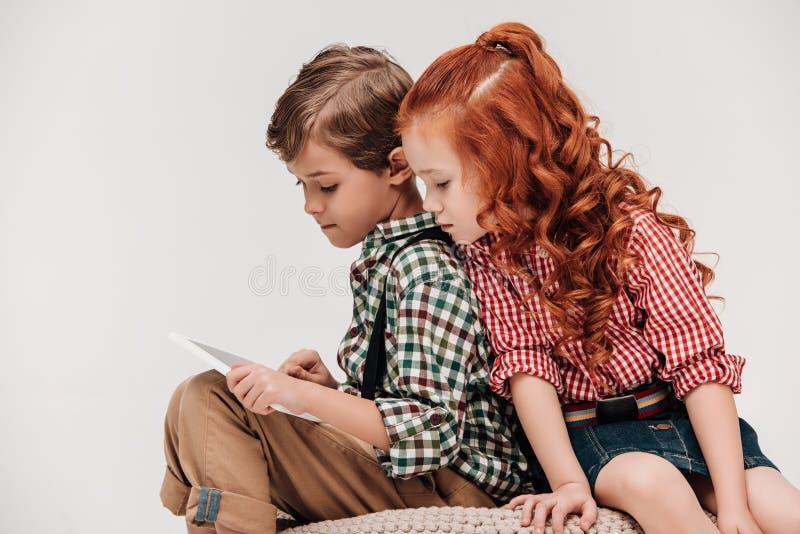 schönes kleines Kind, das den Freund verwendet digitale Tablette betrachtet stockbild