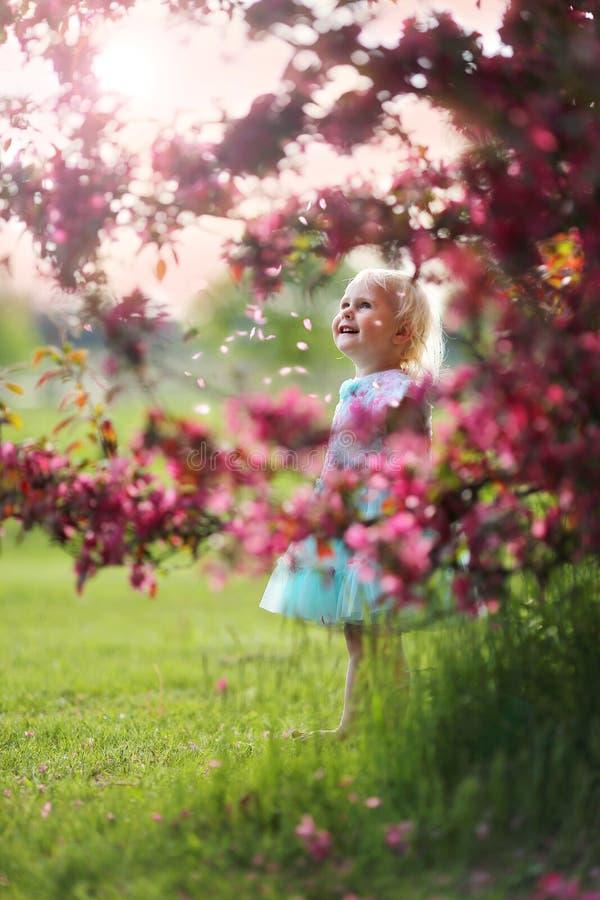 Schönes kleines Kleinkind-Mädchen, das unter dem Blühen von Crabapple steht lizenzfreie stockfotos