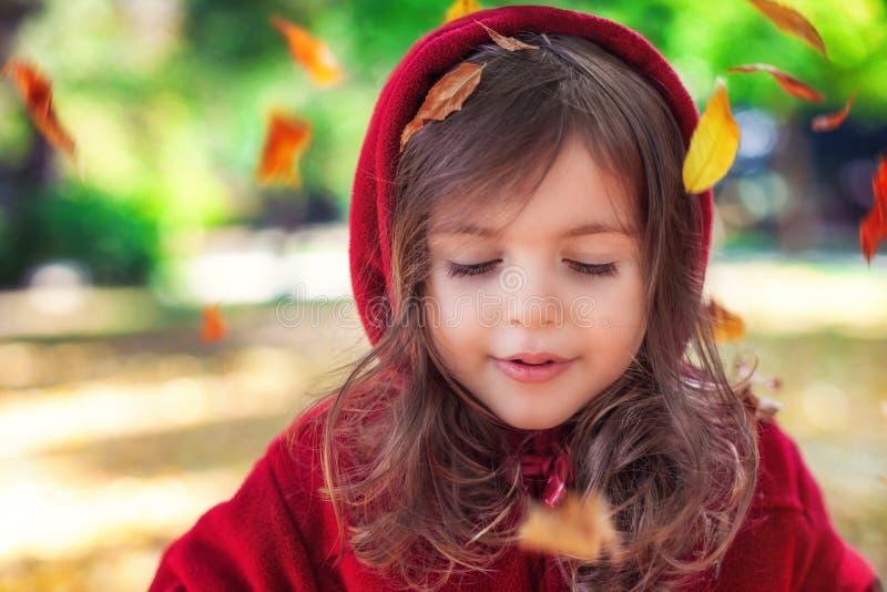 Schönes kleines Mädchen als Rotkäppchen, das mit gefallenen Blättern am Herbstpark spielt lizenzfreie stockbilder