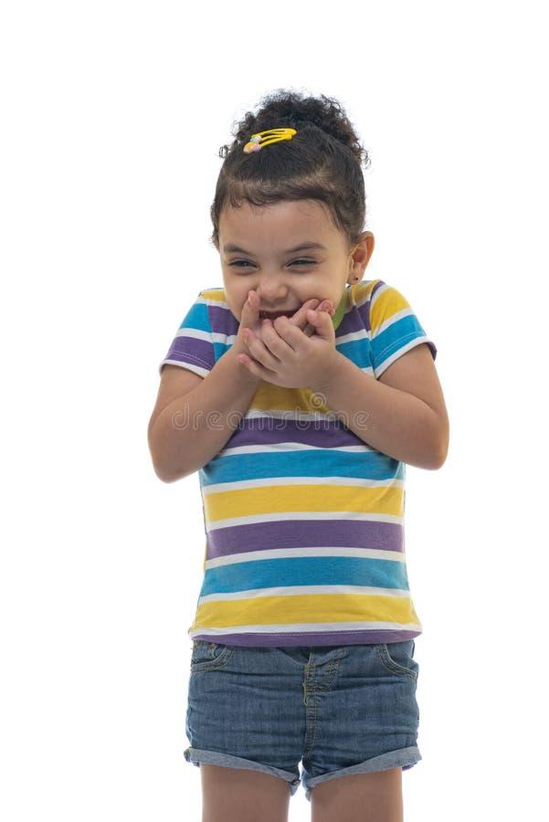 Schönes kleines Mädchen, das über jemand mit weidendem Lächeln, schlechtes glückliches Lächeln lacht lizenzfreies stockfoto