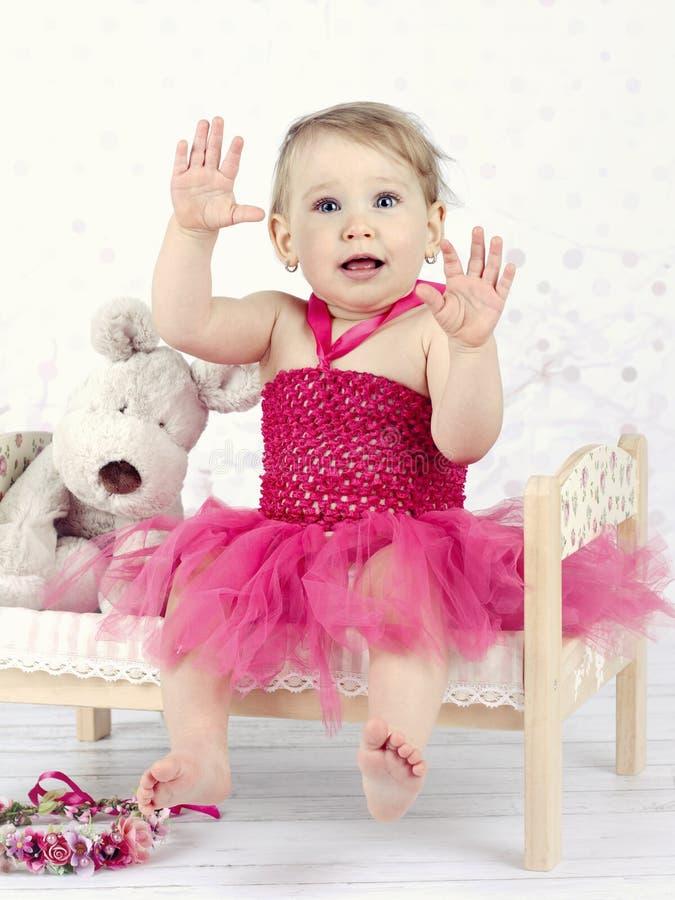 Schönes kleines Mädchen, das auf dem kleinen Blumenbett und dem Lachen sitzt stockbild