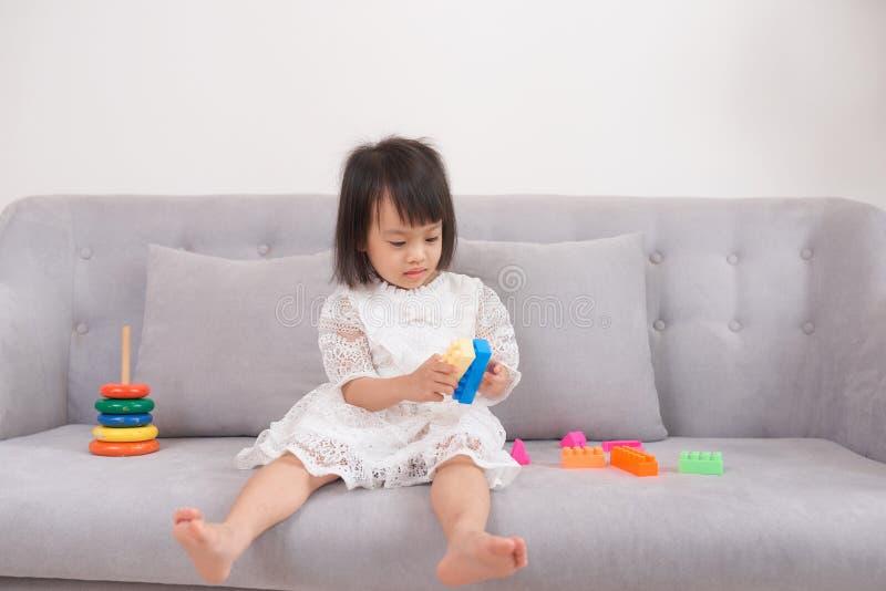Schönes kleines Mädchen, das auf der Couch spielt lizenzfreie stockfotos