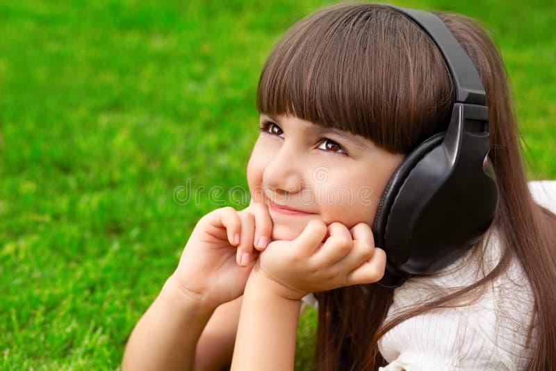 Schönes kleines Mädchen, das auf grünem Gras mit Kopfhörern liegt lizenzfreie stockfotografie