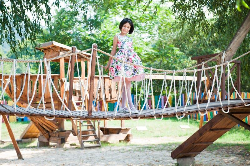 Schönes kleines Mädchen, das auf hängender Brücke am Spielplatz steht lizenzfreie stockbilder
