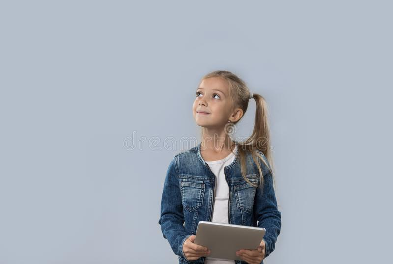 Schönes kleines Mädchen, das den Tablet-Computer oben schaut, um das Raum-glückliche Lächeln zu kopieren lokalisiert verwendet lizenzfreie stockfotos