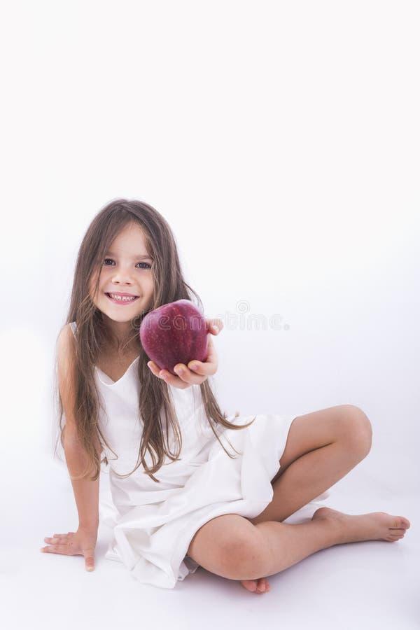 Schönes kleines Mädchen, das einen Apfel anbietet stockfotografie