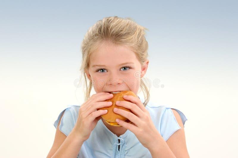 Schönes kleines Mädchen, das einen Cheeseburger isst lizenzfreie stockfotografie