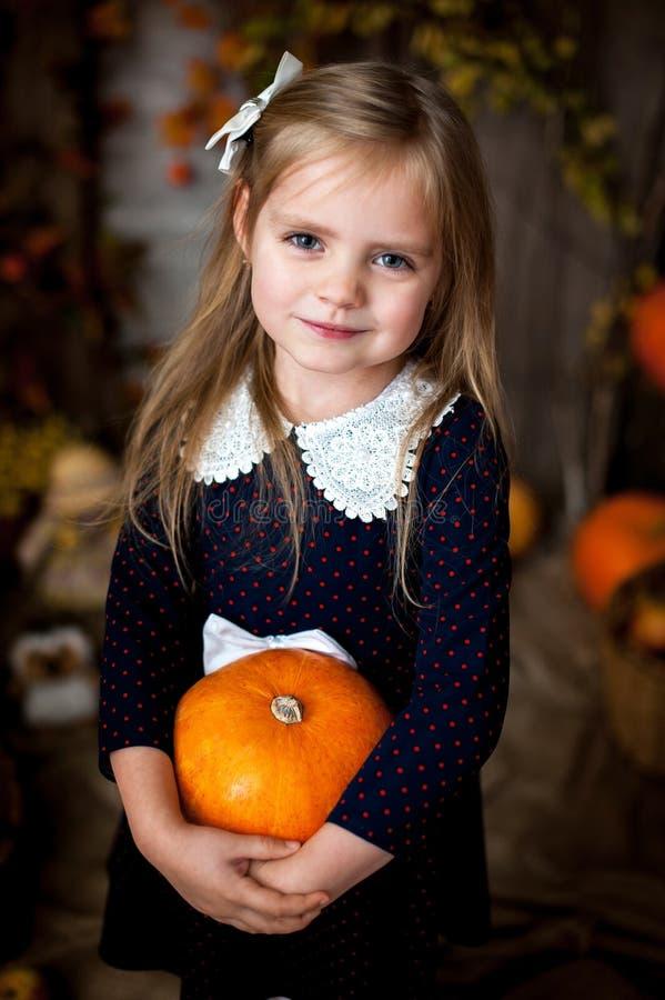 Schönes kleines Mädchen, das einen Kürbis hält lizenzfreie stockfotografie