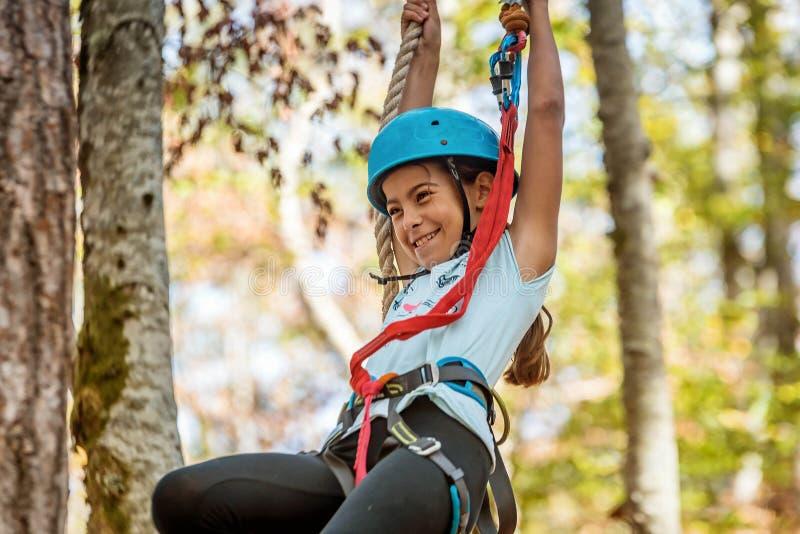 Schönes kleines Mädchen, das im Erlebnispark, Montenegro klettert lizenzfreie stockfotos