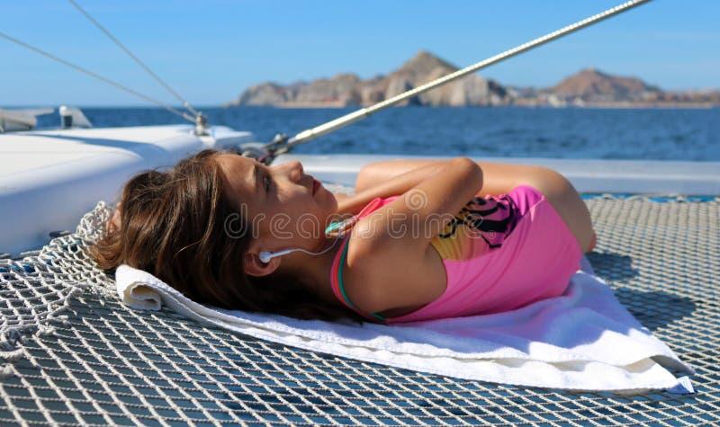 Schönes kleines Mädchen, das im Segelboot beim Hören Musik auf dem Ozean sich entspannt stockfoto
