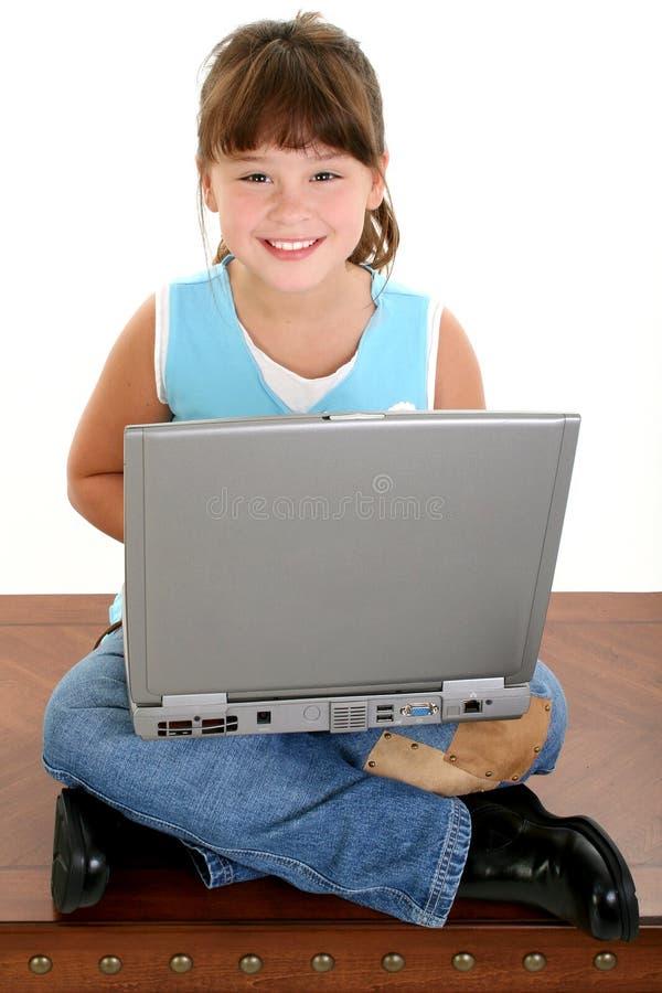 Schönes kleines Mädchen, das an Laptop-Computer arbeitet lizenzfreies stockfoto