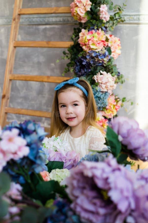 Schönes kleines Mädchen, das mit einem großen Blumenstrauß von lila flowe aufwirft lizenzfreie stockfotografie