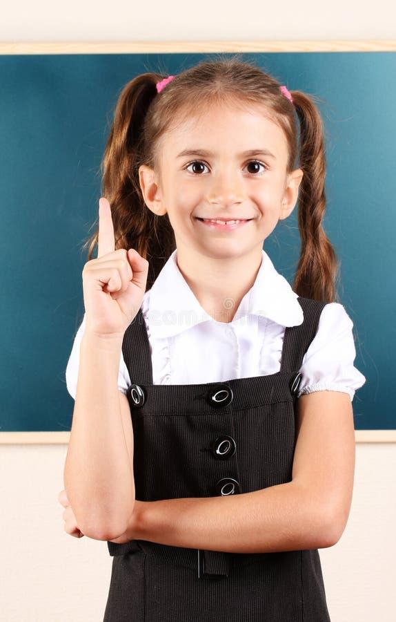 Schönes kleines Mädchen, das nahe Tafel steht stockfoto