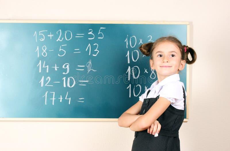 Schönes kleines Mädchen, das nahe Tafel steht stockfotos