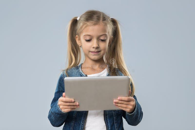 Schönes kleines Mädchen, das Tablet-Computer-den glücklichen lächelnden Abnutzungs-Jeans-Mantel lokalisiert verwendet stockbilder