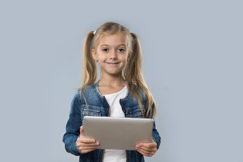 Schönes kleines Mädchen, das Tablet-Computer-den glücklichen lächelnden Abnutzungs-Jeans-Mantel lokalisiert verwendet stockfotografie
