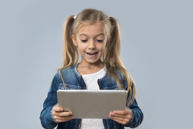 Schönes kleines Mädchen, das Tablet-Computer-den glücklichen lächelnden Abnutzungs-Jeans-Mantel lokalisiert verwendet lizenzfreie stockfotos