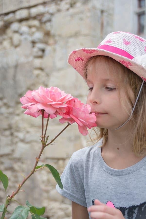 Schönes kleines Mädchen in der rosa Strohmütze, die rosa Rose riecht stockbilder