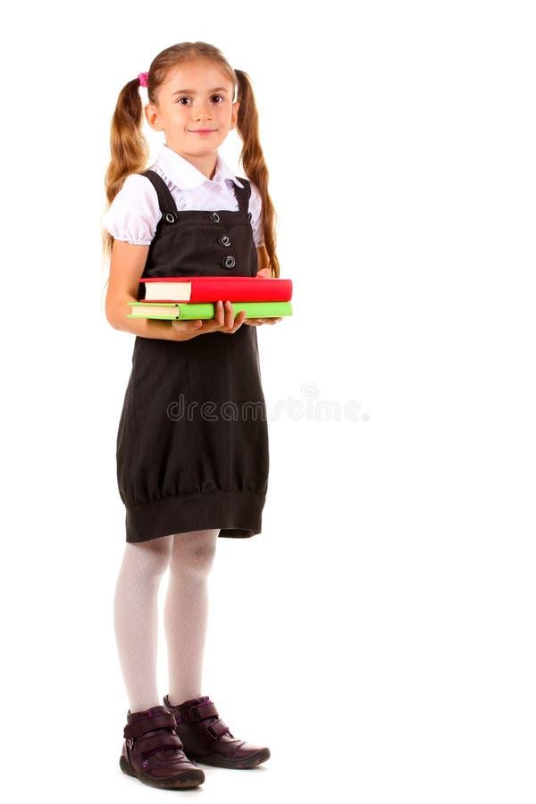 Schönes kleines Mädchen in der Schuluniform und in den Büchern lizenzfreie stockbilder