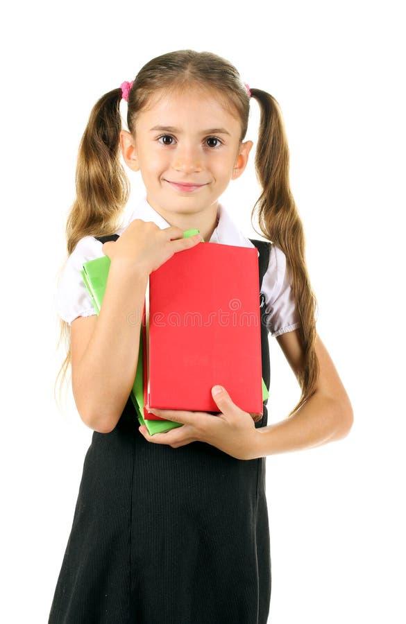 Schönes kleines Mädchen in der Schuluniform und in den Büchern stockfoto