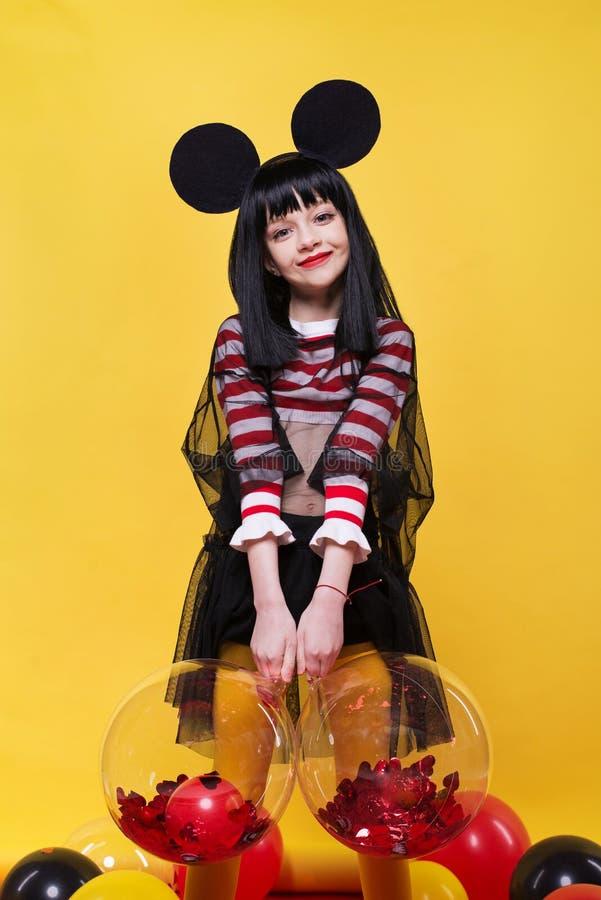 Schönes kleines Mädchen in der schwarzen Perücke, die über hellem gelbem Hintergrund aufwirft lizenzfreies stockbild