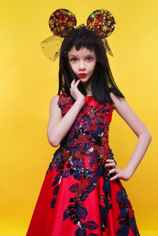 Schönes kleines Mädchen in der schwarzen Perücke, die über hellem gelbem Hintergrund aufwirft lizenzfreie stockfotografie