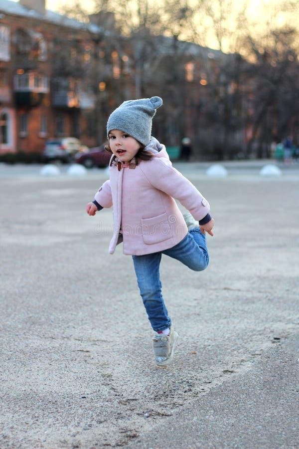 schönes kleines Mädchen in einem Hut, in einem Mantel und in Jeans springt, Fliegen und hat Spaß auf dem Hintergrund des Stadtbil stockbild