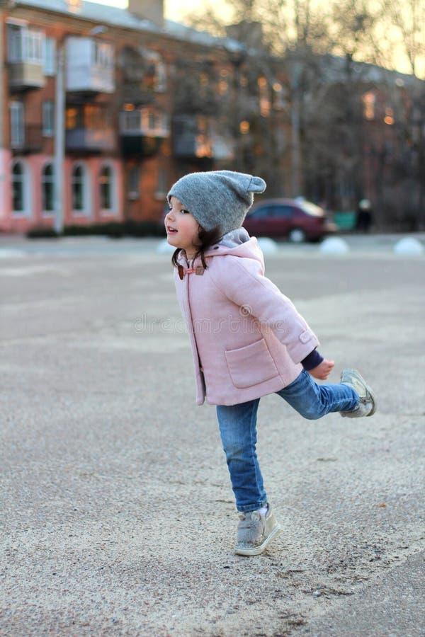 schönes kleines Mädchen in einem Hut, in einem Mantel und in Jeans springt, Fliegen und hat Spaß auf dem Hintergrund des Stadtbil stockbilder