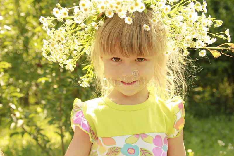 Schönes kleines Mädchen in einem Kranz von Blumen auf der Natur lizenzfreies stockbild