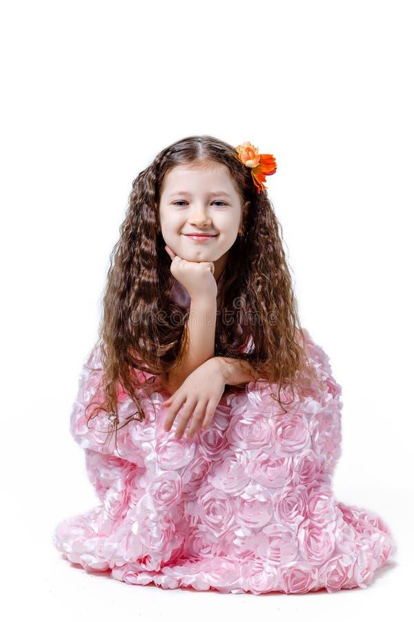 Schönes kleines Mädchen in einem rosa Kleid auf einem weißen Hintergrund stockbild