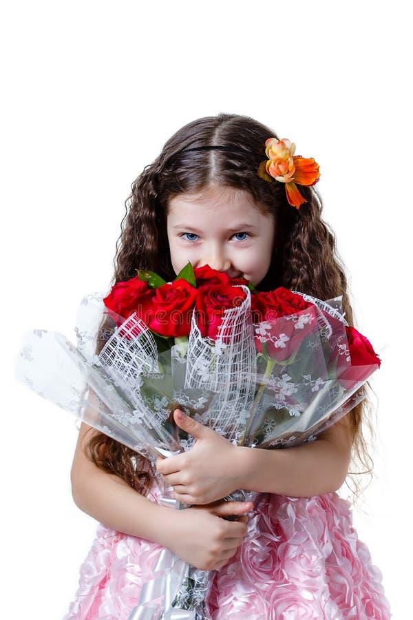Schönes kleines Mädchen in einem rosa Kleid mit einem Blumenstrauß von roten Rosen lizenzfreies stockfoto