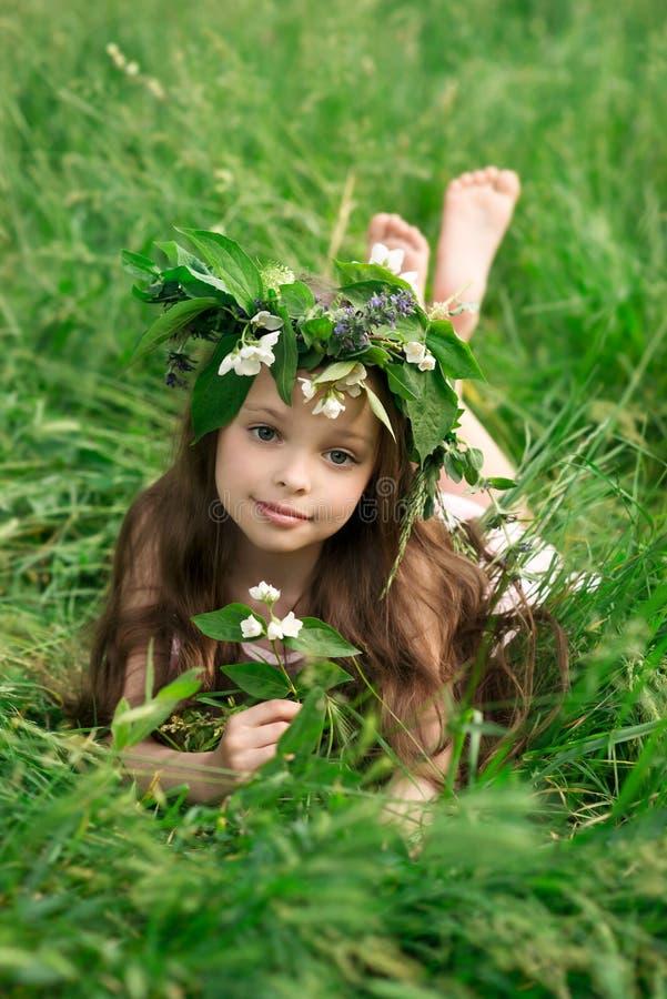 Schönes kleines Mädchen in einem weißen Kleid, das im Gras aufwirft lizenzfreies stockfoto