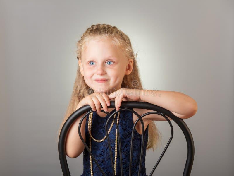 Schönes kleines Mädchen gekleidet in einem dunklen Kleid und in einem Schmuck auf Grau stockfoto