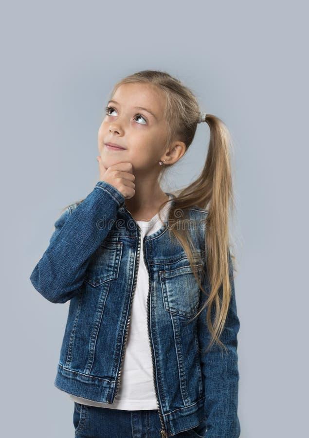 Schönes kleines Mädchen-glückliches lächelndes Abnutzungs-Jeans-Mantel lokalisiertes oben schauen, zum des Raumes zu kopieren lizenzfreies stockbild
