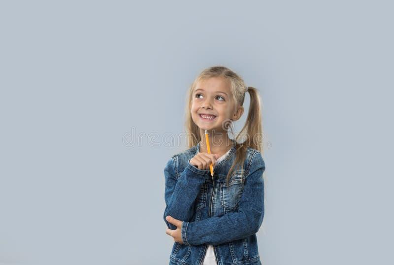 Schönes kleines Mädchen-Griff-Bleistift-Schreiben, welches das glückliche lächelnde Schauen, zum des Raumes zu kopieren lokalisie stockfoto