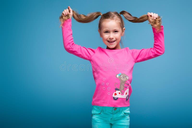 Schönes kleines Mädchen im rosa Hemd mit Affen und blauer Hose lizenzfreie stockfotos