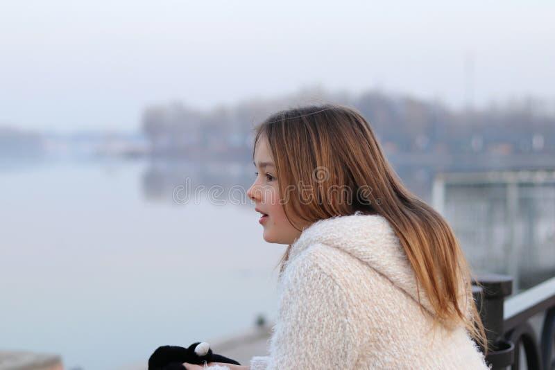 Schönes kleines Mädchen im weißen Mantel, der den Fluss, überrascht betrachtet lizenzfreies stockbild