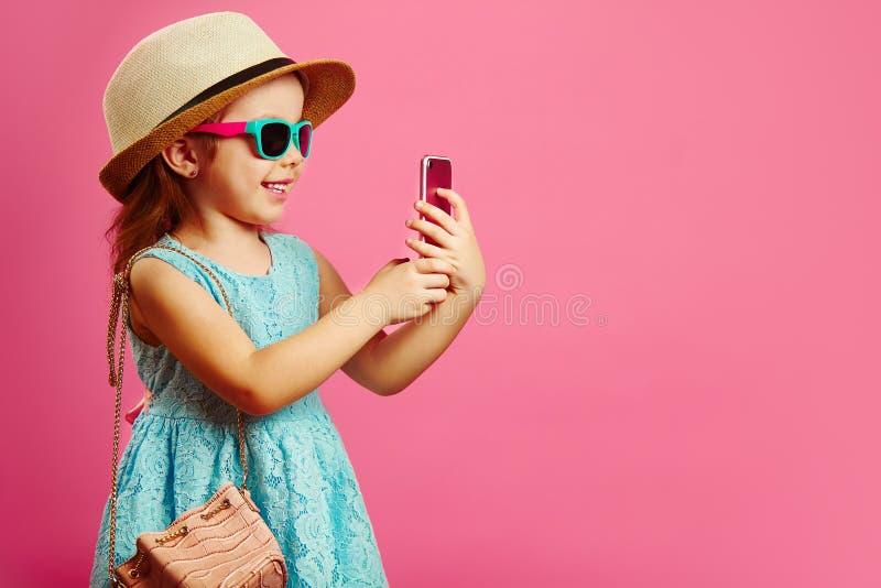 Schönes kleines Mädchen mit bezaubernden Lächelnblicken auf Telefon, lässt eine gute Laune, kleiden im modernen blauen Kleid, das stockfotos