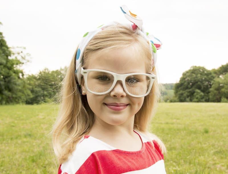 Schönes kleines Mädchen mit dem Glaslächeln lizenzfreies stockfoto