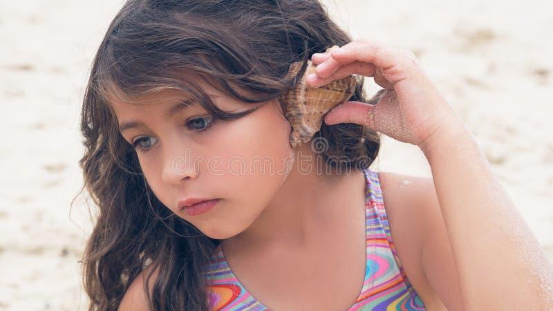 Schönes kleines Mädchen mit dem langen gelockten Haar hörend Seemusik im Cockleshell auf dem Strand stockfotografie
