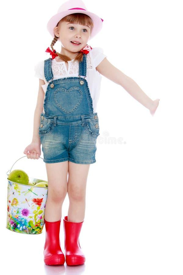 Schönes kleines Mädchen mit einem Eimer Äpfeln stockbild