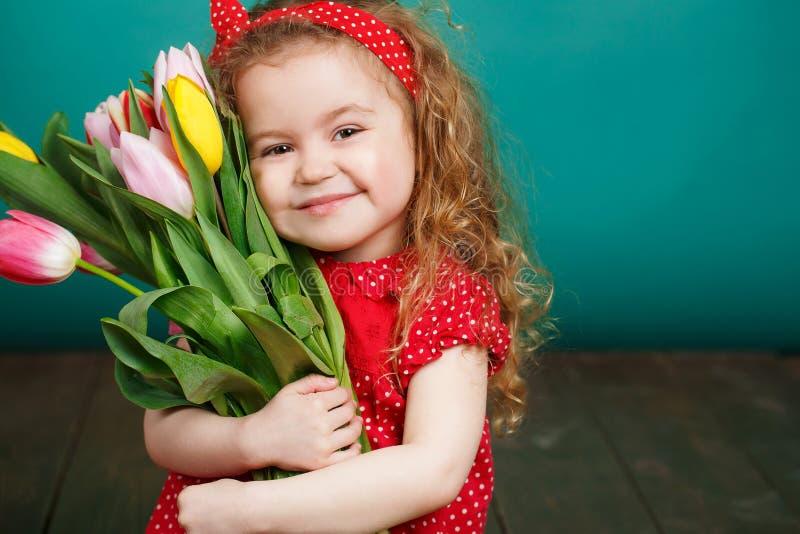 Schönes kleines Mädchen mit einem großen Blumenstrauß von Tulpen lizenzfreie stockfotos
